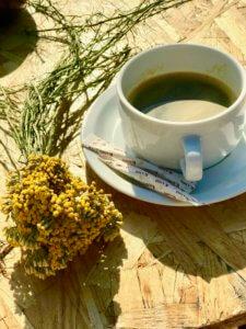 Ein Strauß Immortellen neben einer Tasse Kaffee